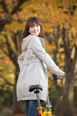 自転車を持ち振り返る笑顔の女性