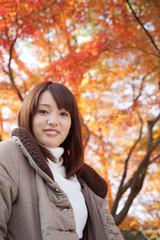 紅葉の下で微笑む女性