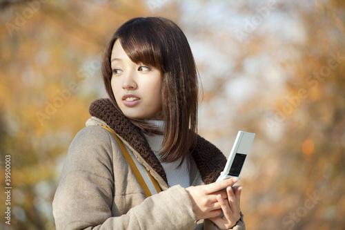 携帯電話を持って振り返る女性