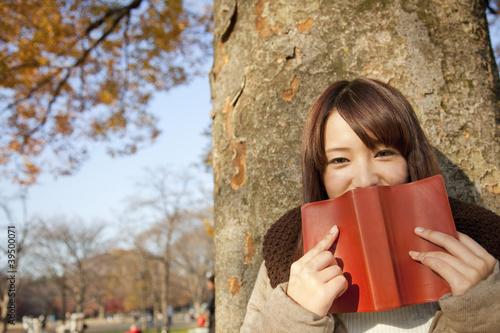 木に寄りかかり本を持つ女性