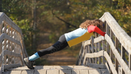 caucasian girl doing push ups on a bridge