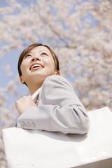 通勤中に桜を見上げるOL
