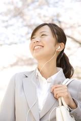音楽を聴きながら桜を見上げる通勤中の女性