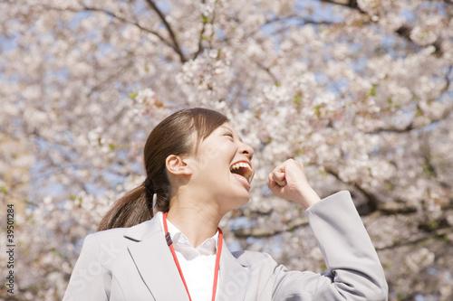 桜の下でガッツポーズをする女性