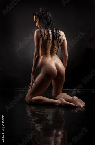 Naked girl in water on a black background