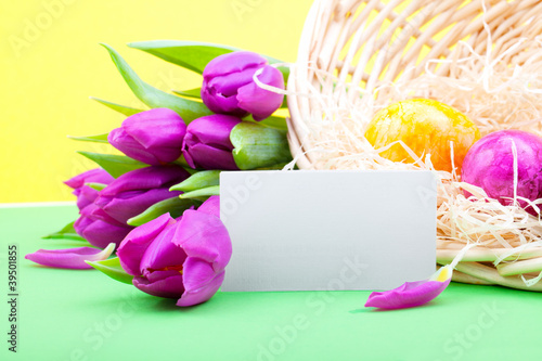 Bouquet of tulips with blank card and Easter eggs