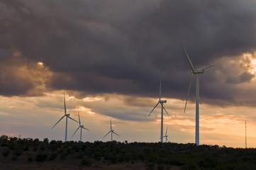 windmills on a hill at sunset with clouds