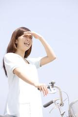 自転車を押しながら空を見上げる女性