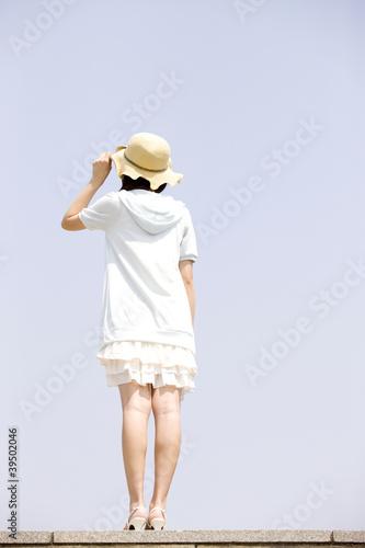 空を眺めている女性の後ろ姿