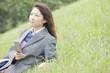 丘に座って携帯電話を触る女子高生