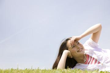 芝生に寝転がり空を眺める女性