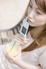ベンチに座り携帯電話を顎に当てて考え事をする女性