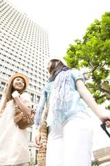 キャリーバックを引いて街中を歩く2人の女性