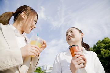 公園のベンチで飲み物を飲む2人の女性