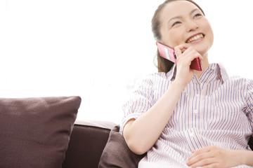 ソファーに座りながら携帯電話で通話する女性
