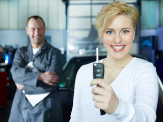 Satisfied customer shows car key, mechanic at the background