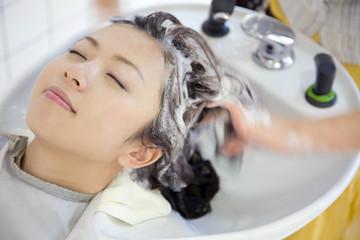 美容院で髪を洗ってもらう女性