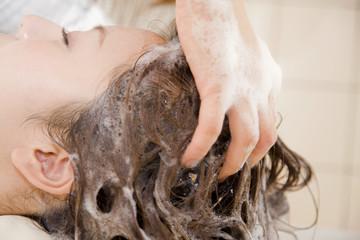 ヘアサロンで髪を洗ってもらう女性