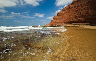 huge red cliffs on the beach Legzira. Morocco