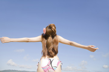 浜辺で両手を広げてリラックスしている水着姿の女性