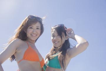 青空の下で微笑む水着女性2人