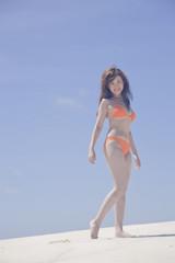 砂浜を歩く水着女性
