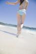 波打ち際を走る水着女性の後姿