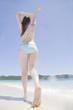 伸びをしながら波打ち際を歩く水着女性の後姿