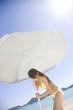ビーチパラソルを砂浜に建てようとしている水着女性