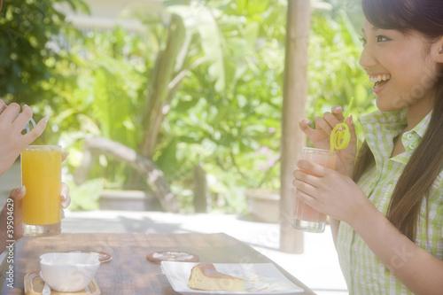 新緑に囲まれたカフェでジュースを飲みながら友達と談笑する女性