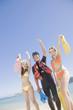 波打ち際でフィンを持って記念撮影をする水着女性2人とウェットスーツを着た男性