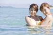 海に入って遊ぶ水着女性2人