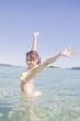 海に入って伸びをする水着女性