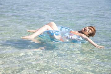 浮き輪に乗って海を泳ぐ水着女性
