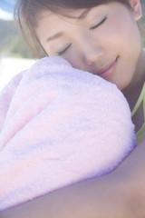 タオルに触れながら瞼を閉じる水着女性