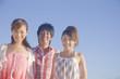 青空の下で微笑む女性2人と男性