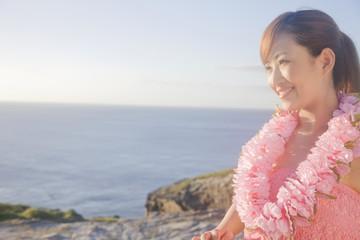 海辺で遠くを眺めるレイをかけた女性