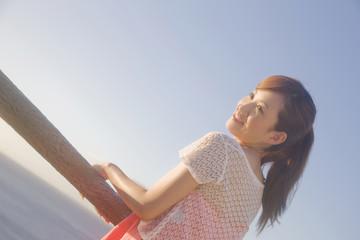海辺で遠くを眺める女性
