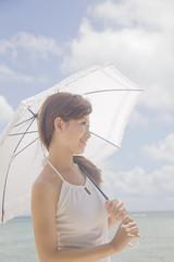 ビーチで日傘を差す女性