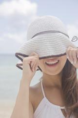 帽子の鍔で目を隠す女性