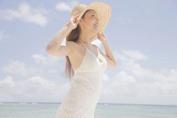 麦わら帽子の鍔を持って空を見上げる女性