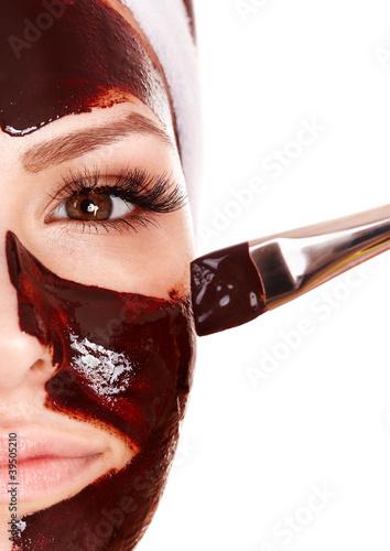 Girl having chocolate facial mask.