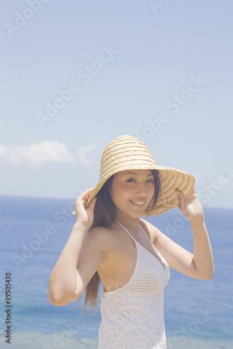 麦わら帽子を被って振り向く女性