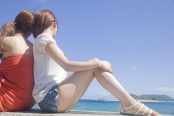 背中合わせで海辺に座る女性2人