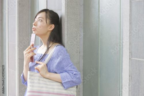 携帯電話を持って上を眺める女性