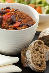 Hot and spicy minced meat chili with fresh bread and salad