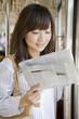 電車で新聞を読む女性