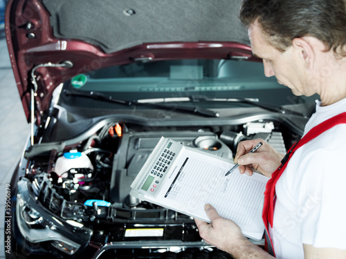 Motor mechanic in front engine bay writing a quotation