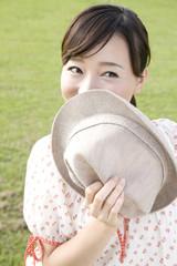 帽子を持って微笑む女性