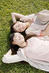 芝生に寝転ぶ女性2人
